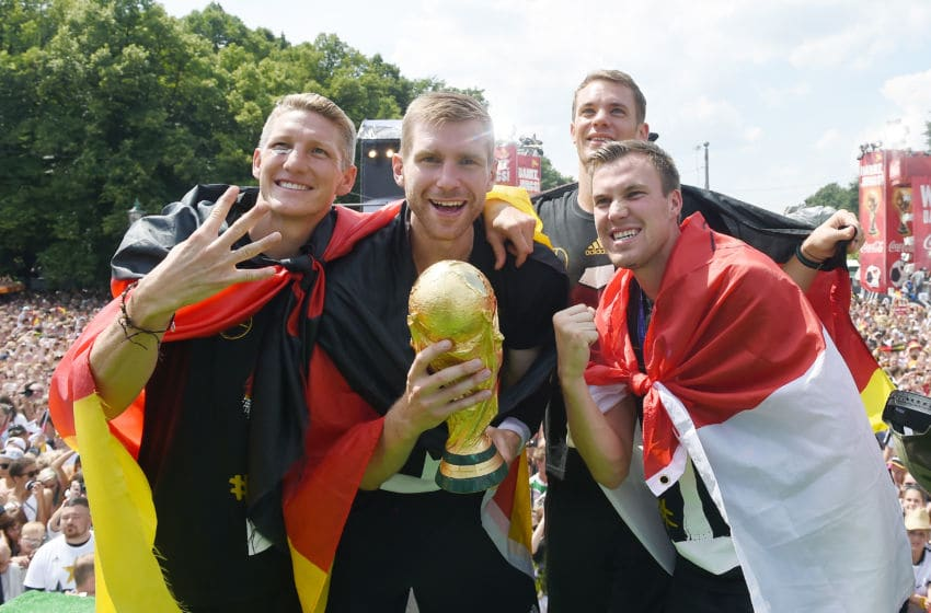 BERLIN, GERMANY - JULY 15: Bastian Schweinsteiger, Per Mertersacker, Manuel Neuer and Kevin Grosskreutz celebrate during the German team victory ceremony on July 15, 2014 in Berlin, Germany. Germany won the 2014 FIFA World Cup Brazil match against Argentina in Rio de Janeiro on July 13. (Photo by Markus Gilliar - Pool /Getty Images)