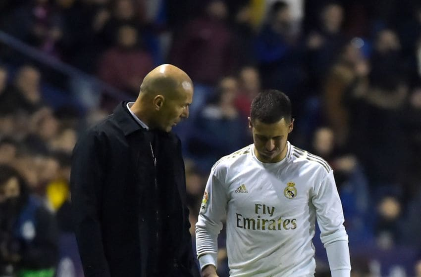 Real Madrid's French coach Zinedine Zidane (L) talks to Real Madrid's Belgian forward Eden Hazard during the Spanish league football match Levante UD against Real Madrid CF at the Ciutat de Valencia stadium in Valencia on February 22, 2020. (Photo by JOSE JORDAN / AFP) (Photo by JOSE JORDAN/AFP via Getty Images)