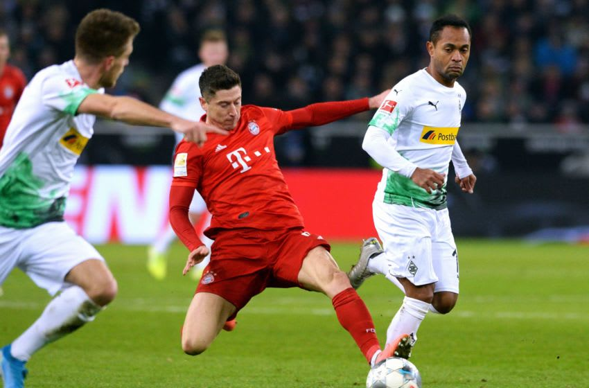 Bayern Munich's Polish forward Robert Lewandowski (C) and Moenchengladbach's Brazilian forward Raffael (R) vie for the ball during the German first division Bundesliga football match Borussia Moenchengladbach vs Bayern Munich in Moenchengladbach, western Germany, on December 7, 2019. (Photo by UWE KRAFT / AFP) / DFL REGULATIONS PROHIBIT ANY USE OF PHOTOGRAPHS AS IMAGE SEQUENCES AND/OR QUASI-VIDEO (Photo by UWE KRAFT/AFP via Getty Images)