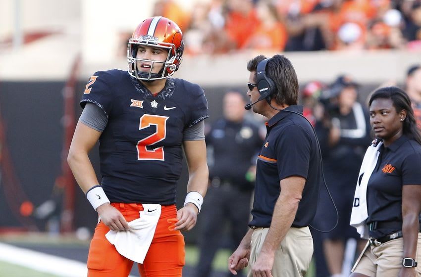 Oct 8, 2016; Stillwater, OK, USA; Oklahoma State Cowboys quarterback Mason Rudolph (2) talks with head coach Mike Gundy before a play against the Iowa State Cyclones during the second half at Boone Pickens Stadium. Oklahoma State won 38-31. Mandatory Credit: Alonzo Adams-USA TODAY Sports