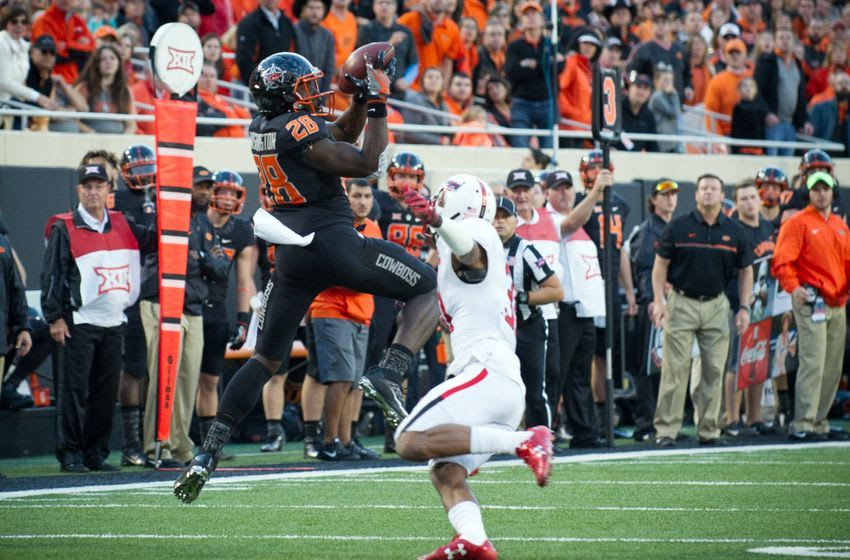 Nov 12, 2016; Stillwater, OK, USA; Oklahoma State Cowboys wide receiver James Washington (28) makes a catch as Texas Tech Red Raiders defensive back Justis Nelson (31) defends during the second half at Boone Pickens Stadium. Cowboys won 45-44. Mandatory Credit: Rob Ferguson-USA TODAY Sports