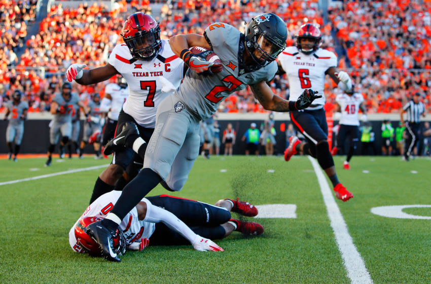 STILLWATER, OK - SEPTEMBER 22: Wide receiver Tylan Wallace #2 of the Oklahoma State Cowboys tries to hurdle past defensive back Adrian Frye #20 of the Texas Tech Red Raiders as defensive back Jah'Shawn Johnson #7 pursues from behind in the first quarter on September 22, 2018 at Boone Pickens Stadium in Stillwater, Oklahoma. (Photo by Brian Bahr/Getty Images)
