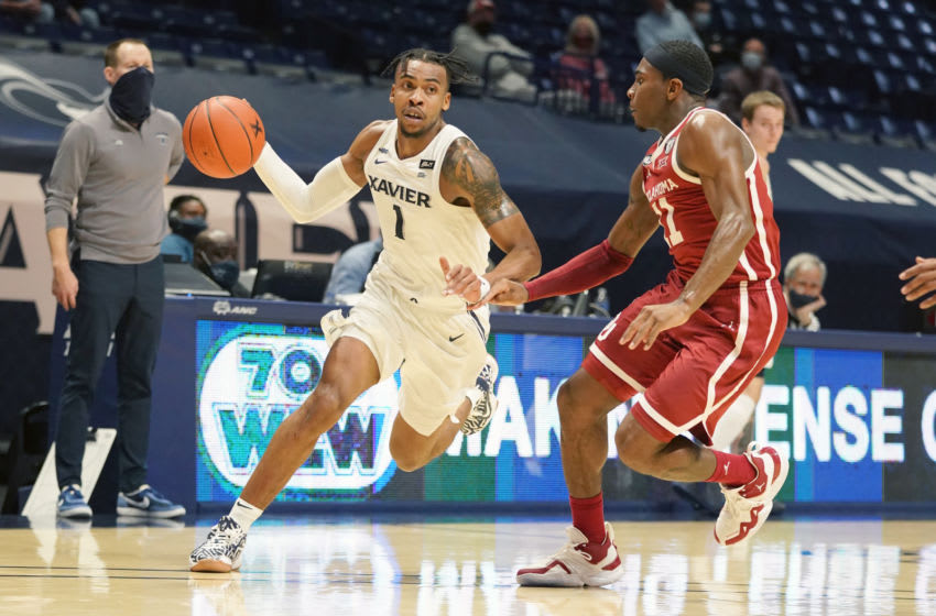CINCINNATI, OH - DECEMBER 09: Paul Scruggs #1 of the Xavier Musketeers dribbles by De'Vion Harmon #11 of the Oklahoma Sooners in the second half during a college basketball game against the Oklahoma Sooners on December 9, 2020 at the Cintas Center in Cincinnati, Ohio. (Photo by Mitchell Layton/Getty Images)