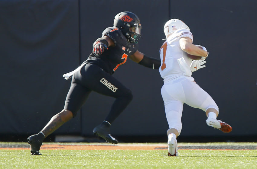 STILLWATER, OK - OCTOBER 31: Linebacker Amen Ogbongbemiga #7 of the Oklahoma State Cowboys pursues wide receiver Jake Smith #7 of the Texas Longhorns on a 10-yard gain to the five yard line to set up a touchdown in the first quarter at Boone Pickens Stadium on October 31, 2020 in Stillwater, Oklahoma. Texas won 41-34 in overtime. (Photo by Brian Bahr/Getty Images)