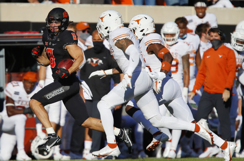 STILLWATER, OK - OCTOBER 31: Wide receiver Braydon Johnson #8 of the Oklahoma State Cowboys turns a catch into a 41-yard gain against defensive back Caden Sterns #7 and defensive back B.J. Foster #25 of the Texas Longhorns in the second quarter at Boone Pickens Stadium on October 31, 2020 in Stillwater, Oklahoma. Texas won 41-34 in overtime. (Photo by Brian Bahr/Getty Images)