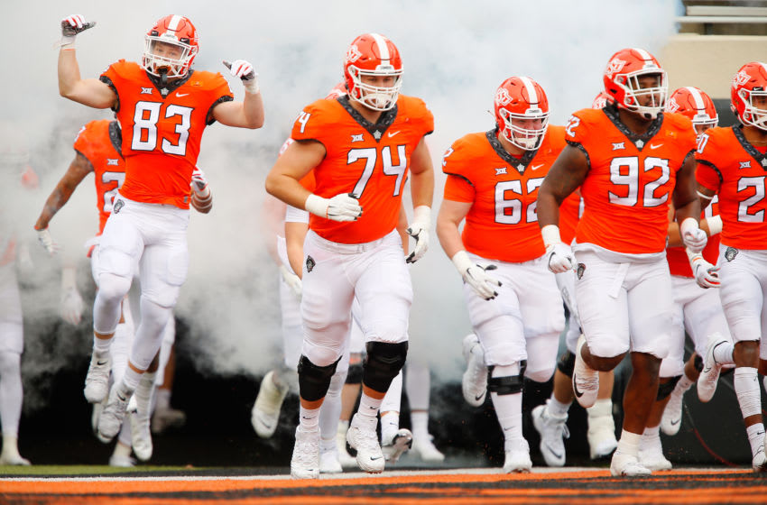 STILLWATER, OK - NOVEMBER 28: Wide receiver Cade Cavender #83, left guard Preston Wilson #74, right guard Cade Bennett #62, and defensive tackle Cameron Murray #92 of the Oklahoma State Cowboys run on to the field for a game against the Texas Tech Red Raiders at Boone Pickens Stadium on November 28, 2020 in Stillwater, Oklahoma. OSU won 50-44. (Photo by Brian Bahr/Getty Images)