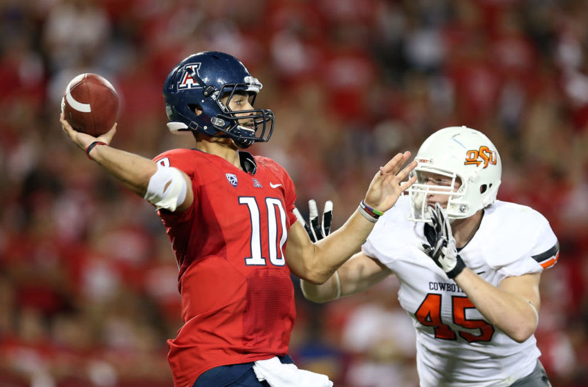 TUCSON, AZ - SEPTEMBER 08: Quarterback Matt Scott #10 of the Arizona Wildcats throws a pass under pressure from linebacker Caleb Lavey #45 of the Oklahoma State Cowboys during the college football game at Arizona Stadium on September 8, 2012 in Tucson, Arizona. The Wildcats defeated the Cowboys 59-38. (Photo by Christian Petersen/Getty Images)