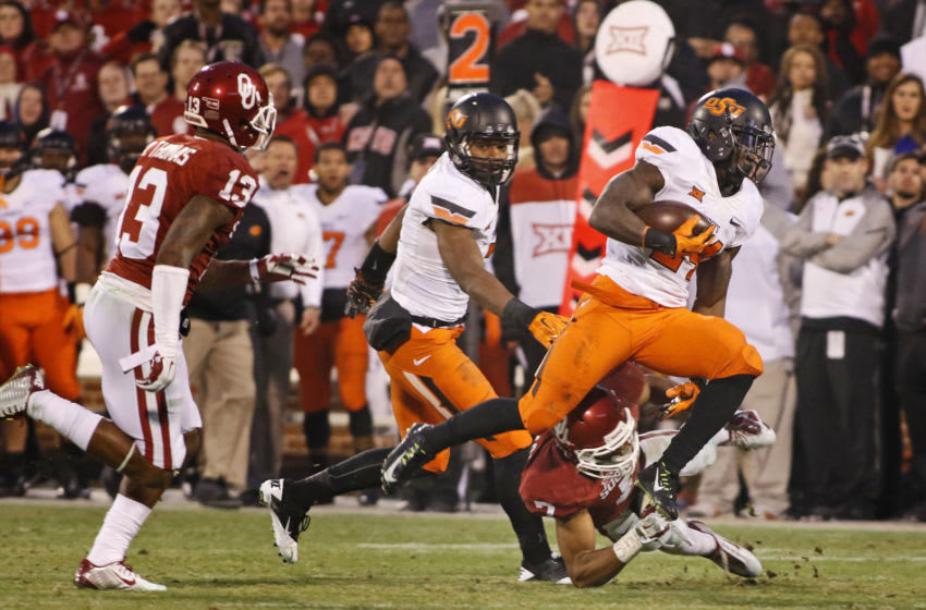 NORMAN, OK - DECEMBER 6: Wide receiver Tyreek Hill #24 of the Oklahoma State Cowboys is hit by cornerback Jordan Thomas #7 of the Oklahoma Sooners December 6, 2014 at Gaylord Family-Oklahoma Memorial Stadium in Norman, Oklahoma. The Cowboys defeated the Sooners 38-35 in overtime. (Photo by Brett Deering/Getty Images)