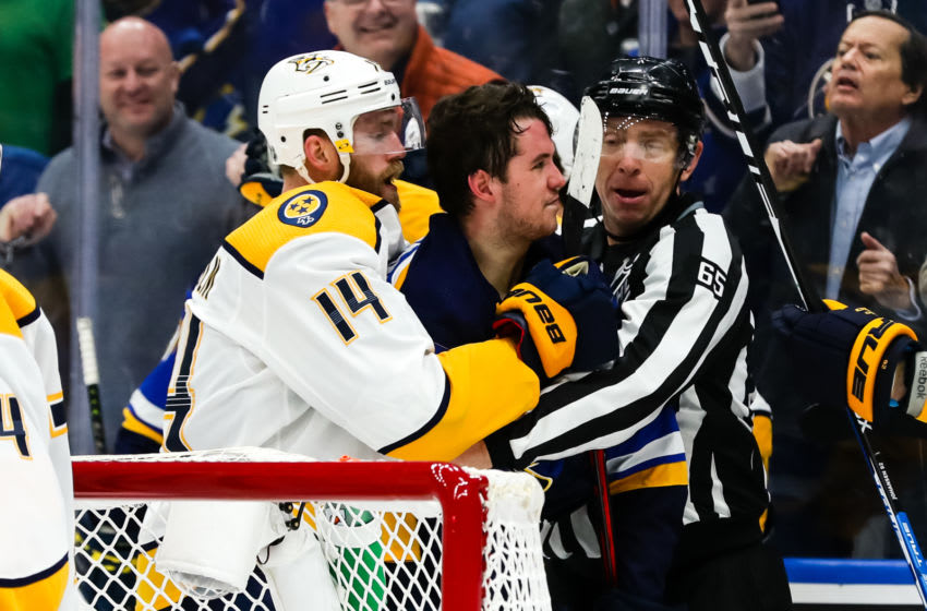 ST. LOUIS, MO - FEBRUARY 26: St. Louis Blues' Mackenzie MacEachern, center, is held back by Nashville Predators' Mattias Ekholm and linesman Pierre Racicot, right, during the second period of an NHL hockey game between the St. Louis Blues and the Nashville Predators on February 26, 2019, at the Enterprise Center in St. Louis, MO. (Photo by Tim Spyers/Icon Sportswire via Getty Images)