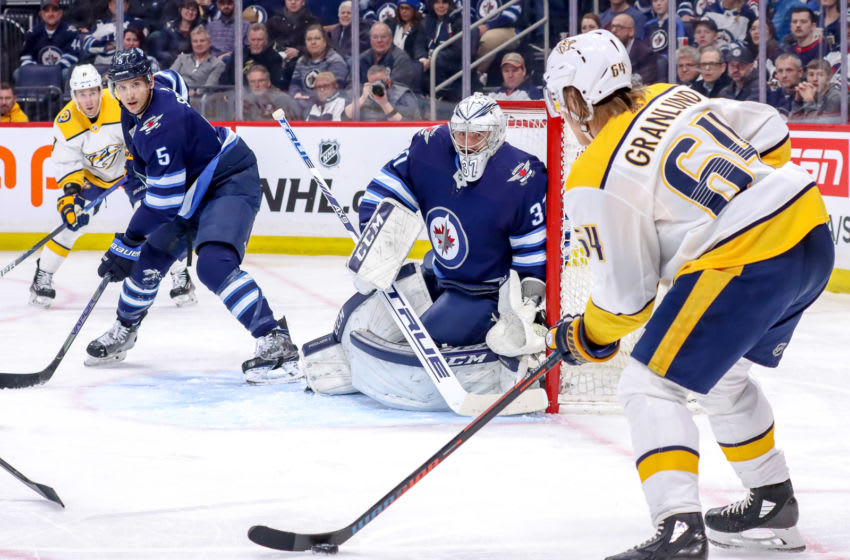 WINNIPEG, MB - FEBRUARY 4: Mikael Granlund #64 of the Nashville Predators plays the puck as Luca Sbisa #5 and goaltender Connor Hellebuyck #37 of the Winnipeg Jets defend the net during second period action at the Bell MTS Place on February 4, 2020 in Winnipeg, Manitoba, Canada. (Photo by Darcy Finley/NHLI via Getty Images)