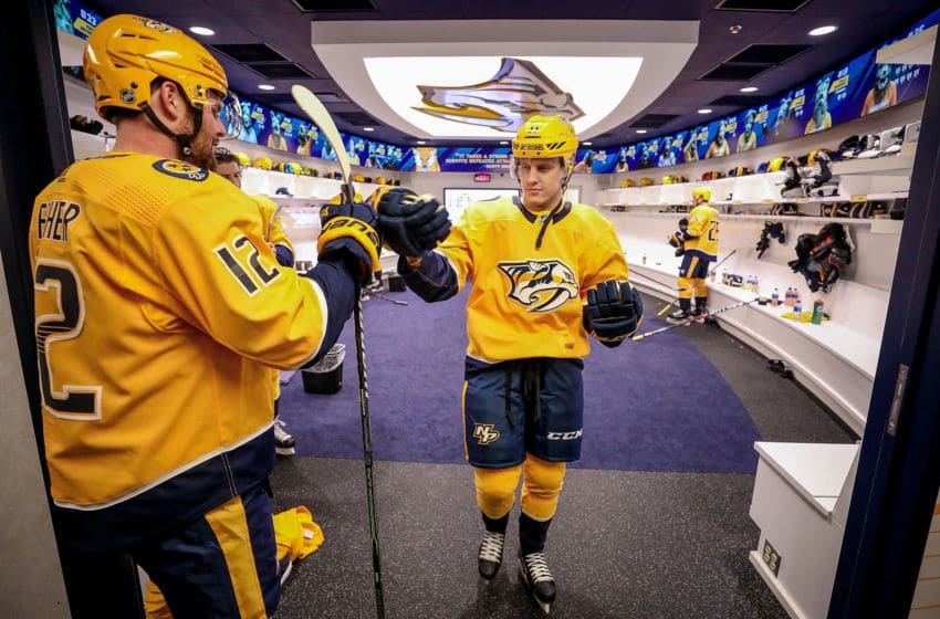 NASHVILLE, TN - MARCH 31: Mike Fisher #12 playing his 1100th career game taps gloves with Eeli Tolvanen #11 of the Nashville Predators as he walks to the ice for his NHL debut against the Buffalo Sabres at Bridgestone Arena on March 31, 2018 in Nashville, Tennessee. (Photo by John Russell/NHLI via Getty Images)