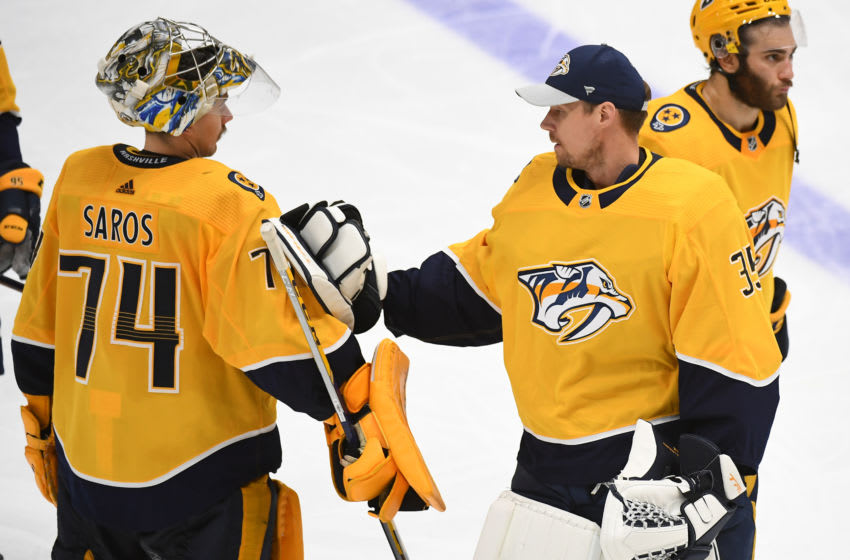 Nashville Predators goaltender Juuse Saros (74) meets with goaltender Pekka Rinne (35) after an overtime loss against the Carolina Hurricanes in game six of the first round of the 2021 Stanley Cup Playoffs at Bridgestone Arena. Mandatory Credit: Christopher Hanewinckel-USA TODAY Sports