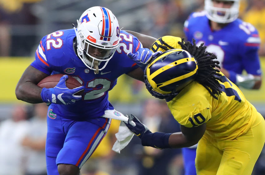 ARLINGTON, TX - SEPTEMBER 02: Lamical Perine #22 of the Florida Gators holds off Devin Bush #10 of the Michigan Wolverines on a carry in the second quarter of a game at AT&T Stadium on September 2, 2017 in Arlington, Texas. (Photo by Tom Pennington/Getty Images)