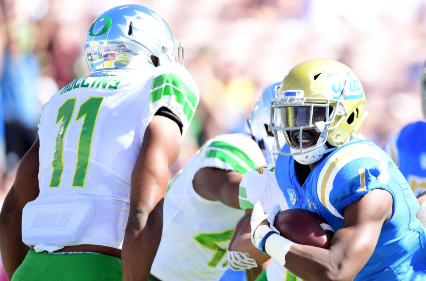 PASADENA, CA - OCTOBER 21: Soso Jamabo #1 of the UCLA Bruins scores a touchdown for a 7-0 lead in front of Justin Hollins #11 of the Oregon Ducks during the first half at Rose Bowl on October 21, 2017 in Pasadena, California. (Photo by Harry How/Getty Images)