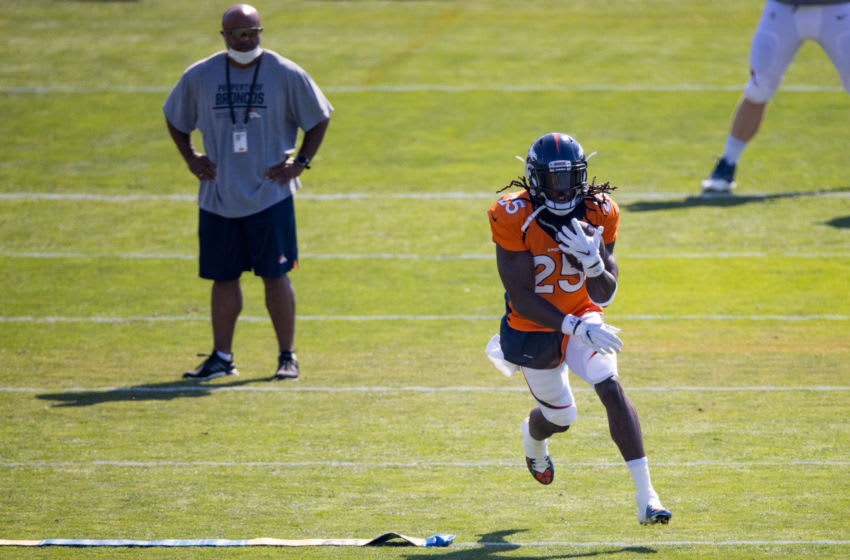 ENGLEWOOD, CO - AUGUST 18: Running back Melvin Gordon #25 of the Denver Broncos runs with the football as Running Backs Coach Curtis Modkins looks on during a training session at UCHealth Training Center on August 18, 2020 in Englewood, Colorado. (Photo by Justin Edmonds/Getty Images)