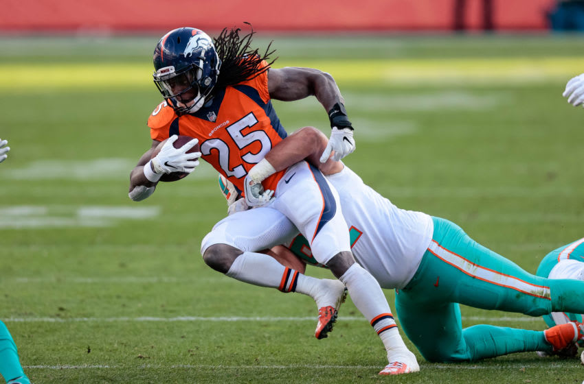 Nov 22, 2020; Denver, Colorado, USA; Denver Broncos running back Melvin Gordon III (25) is tackled by Miami Dolphins defensive tackle Zach Sieler (92) in the second quarter at Empower Field at Mile High. Mandatory Credit: Isaiah J. Downing-USA TODAY Sports
