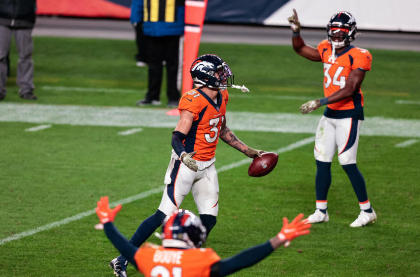 Nov 22, 2020; Denver, Colorado, USA; Denver Broncos safety Justin Simmons (31) celebrates his interception against the Miami Dolphins as cornerback A.J. Bouye (21) and cornerback Essang Bassey (34) react in the fourth quarter at Empower Field at Mile High. Mandatory Credit: Isaiah J. Downing-USA TODAY Sports
