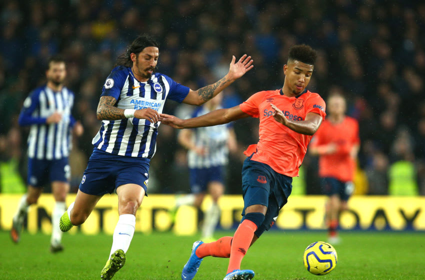 BRIGHTON, ENGLAND - OCTOBER 26: Mason Holgate of Everton runs with the ball under pressure from Ezequiel Schelotto of Brighton and Hove Albion during the Premier League match between Brighton & Hove Albion and Everton FC at American Express Community Stadium on October 26, 2019 in Brighton, United Kingdom. (Photo by Charlie Crowhurst/Getty Images)