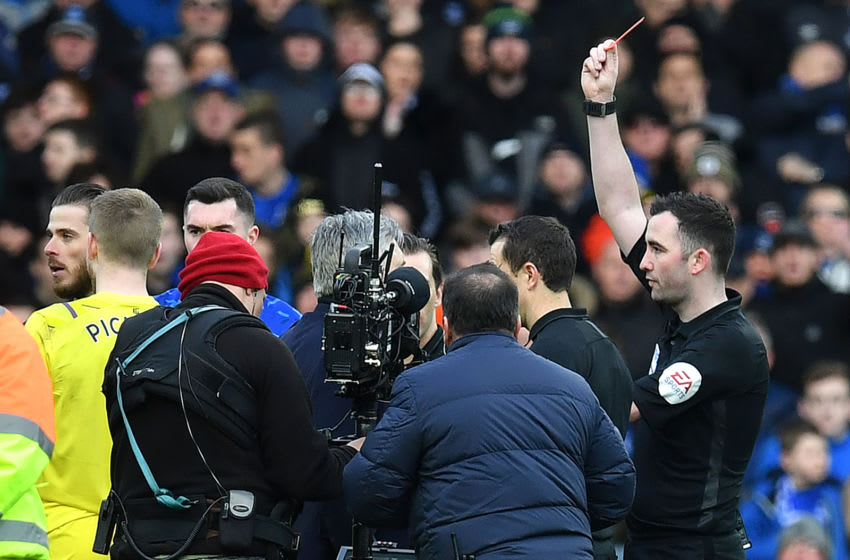 Referee Chris Kavanagh (R) shows a red card to shows a red card to (obstructed) during the English Premier League football match between Everton and Manchester United at Goodison Park in Manchester United, north west England on March 1, 2020. (Photo by Paul ELLIS / AFP) / RESTRICTED TO EDITORIAL USE. No use with unauthorized audio, video, data, fixture lists, club/league logos or 'live' services. Online in-match use limited to 120 images. An additional 40 images may be used in extra time. No video emulation. Social media in-match use limited to 120 images. An additional 40 images may be used in extra time. No use in betting publications, games or single club/league/player publications. / (Photo by PAUL ELLIS/AFP via Getty Images)