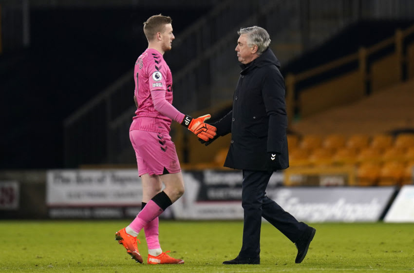 Everton's English goalkeeper Jordan Pickford (L) shakes hands with Everton's Italian head coach Carlo Ancelotti (R) at the end of the match during the English Premier League football match between Wolverhampton Wanderers and Everton at the Molineux stadium in Wolverhampton, central England on January 12, 2021. - Everton won the game 2-1. (Photo by Tim Keeton / POOL / AFP) / RESTRICTED TO EDITORIAL USE. No use with unauthorized audio, video, data, fixture lists, club/league logos or 'live' services. Online in-match use limited to 120 images. An additional 40 images may be used in extra time. No video emulation. Social media in-match use limited to 120 images. An additional 40 images may be used in extra time. No use in betting publications, games or single club/league/player publications. / (Photo by TIM KEETON/POOL/AFP via Getty Images)