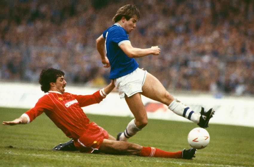 LONDON, UNITED KINGDOM - MARCH 25: Liverpool defender Mark Lawrenson slides in on Everton striker Adrian Heath during the 1984 Milk Cup Final at Wembley Stadium on March 25, 1984 in London, England. (Photo by Allsport/Getty Images)