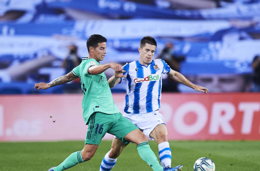 SAN SEBASTIAN, SPAIN - JUNE 21: James Rodríguez of Real Madrid is tackled by Igor Zubeldia of Real Sociedad during the Liga match between Real Sociedad and Real Madrid CF at Estadio Anoeta on June 21, 2020 in San Sebastian, Spain. (Photo by Juan Manuel Serrano Arce/Getty Images)