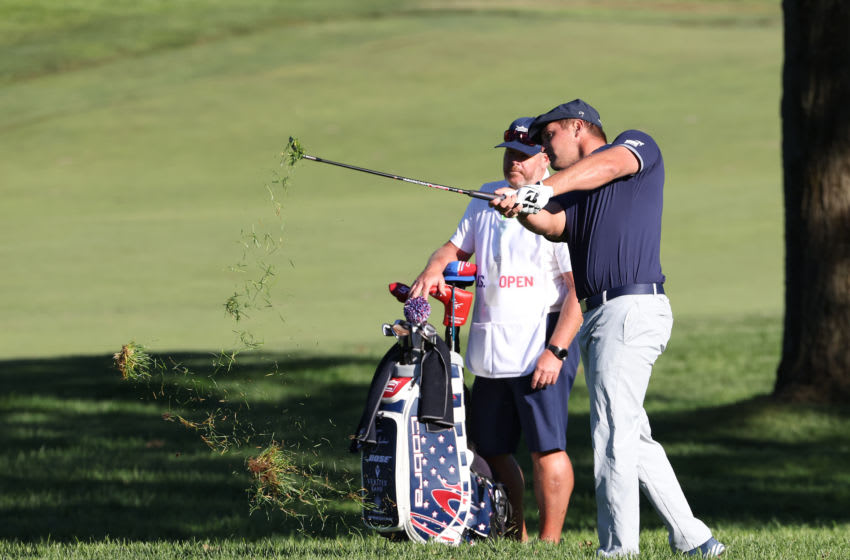 MAMARONECK, NEW YORK - SEPTEMBER 19: Bryson DeChambeau of the United States plays his second shot on the 11th hole as caddie Tim Tucker looks on during the third round of the 120th U.S. Open Championship on September 19, 2020 at Winged Foot Golf Club in Mamaroneck, New York. (Photo by Jamie Squire/Getty Images)