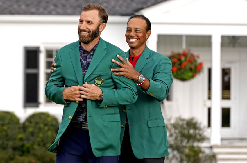 Nov 15, 2020; Augusta, Georgia, USA; 2019 Masters champion Tiger Woods presents Dustin Johnson with the green jacket after winning The Masters golf tournament at Augusta National GC. Mandatory Credit: Rob Schumacher-USA TODAY Sports