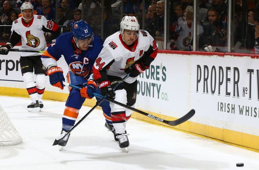 NEW YORK, NEW YORK - NOVEMBER 05: Anders Lee #27 of the New York Islanders and Jean-Gabriel Pageau #44 of the Ottawa Senators battle for the puck at Barclays Center on November 05, 2019 in New York City. (Photo by Mike Stobe/NHLI via Getty Images)