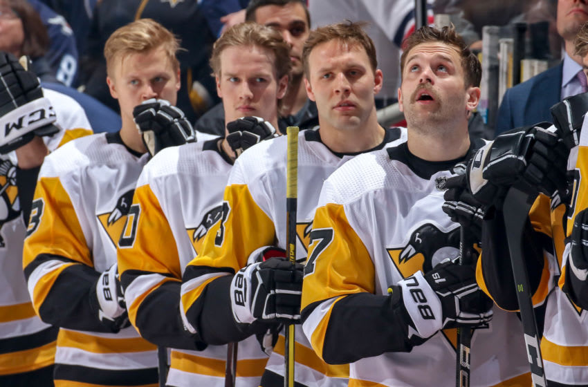 WINNIPEG, MB - NOVEMBER 27: (R-L) Bryan Rust #17, Jack Johnson #73, Juuso Riikola #50 and Olli Maatta #3 of the Pittsburgh Penguins stand on the bench during the singing of the National anthems prior to puck drop against the Winnipeg Jets at the Bell MTS Place on November 27, 2018 in Winnipeg, Manitoba, Canada. (Photo by Jonathan Kozub/NHLI via Getty Images)