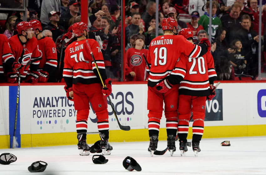 RALEIGH, NC - DECEMBER 07: Sebastian Aho #20 of the Carolina Hurricanes celebrates his hat trick goal with Dougie Hamilton #19 and teammates during an NHL game against the the Minnesota Wild on December 7, 2019 at PNC Arena in Raleigh, North Carolina. (Photo by Gregg Forwerck/NHLI via Getty Images)