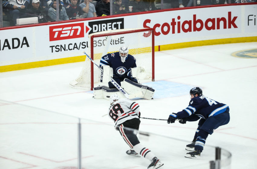 WINNIPEG, MB December 19: Chicago Blackhawks forward Patrick Kane (88) scores on Winnipeg Jets goalie Connor Hellebuyck (37) during the regular season game between the Winnipeg Jets and the Chicago Blackhawks on December 19, 2019 at the Bell MTS Place in Winnipeg MB. (Photo by Terrence Lee/Icon Sportswire via Getty Images)