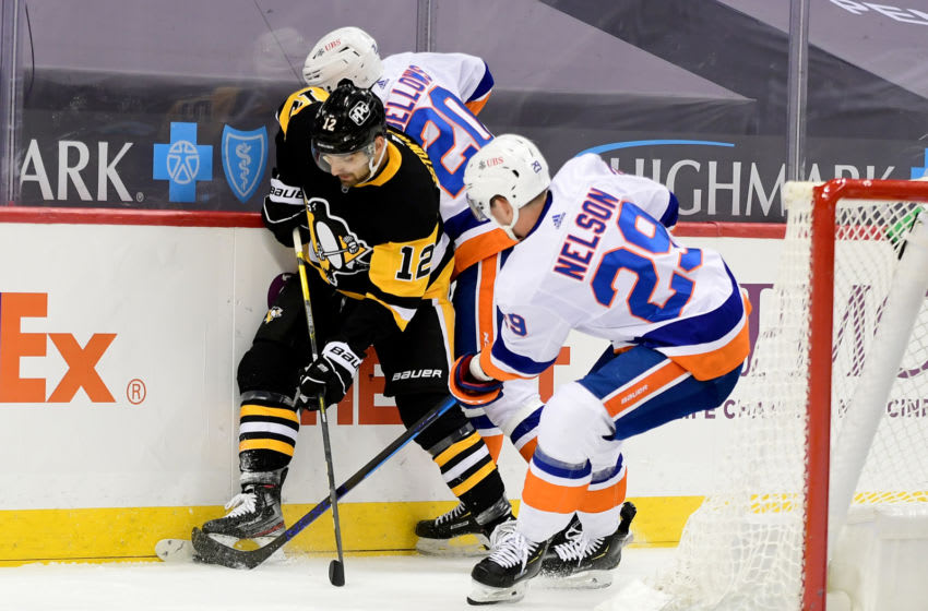 PITTSBURGH, PENNSYLVANIA - FEBRUARY 18: Zach Aston-Reese #12 of the Pittsburgh Penguins competes for the puck with Brock Nelson #29 and Kieffer Bellows #20 of the New York Islanders during their game at PPG PAINTS Arena on February 18, 2021 in Pittsburgh, Pennsylvania. (Photo by Emilee Chinn/Getty Images)