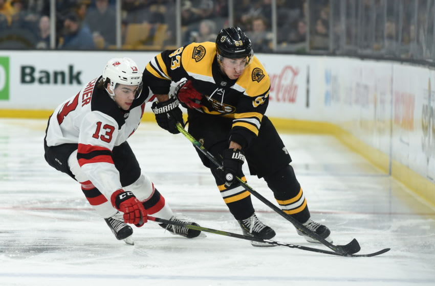 BOSTON, MA - MARCH 2: Brad Marchand #63 of the Boston Bruins skates with the puck against Nico Hischier #13 of the New Jersey Devils at the TD Garden on March 2, 2019 in Boston, Massachusetts. (Photo by Steve Babineau/NHLI via Getty Images)