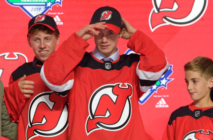 VANCOUVER, BC - JUNE 21: Jack Hughes puts on a hat after being selected first overall by the New Jersey Devils during the first round of the 2019 NHL Draft at Rogers Arena on June 21, 2019 in Vancouver, British Columbia, Canada. (Photo by Derek Cain/Icon Sportswire via Getty Images)