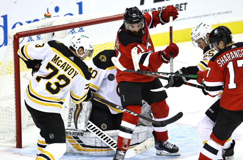 NEWARK, NEW JERSEY - JANUARY 14: Tuukka Rask #40 of the Boston Bruins is unable to stop a shot by Ty Smith #24 of the New Jersey Devils as Kyle Palmieri #21 of the Devils block in front in the third period during the home opening game at Prudential Center on January 14, 2021 in Newark, New Jersey. (Photo by Elsa/Getty Images)