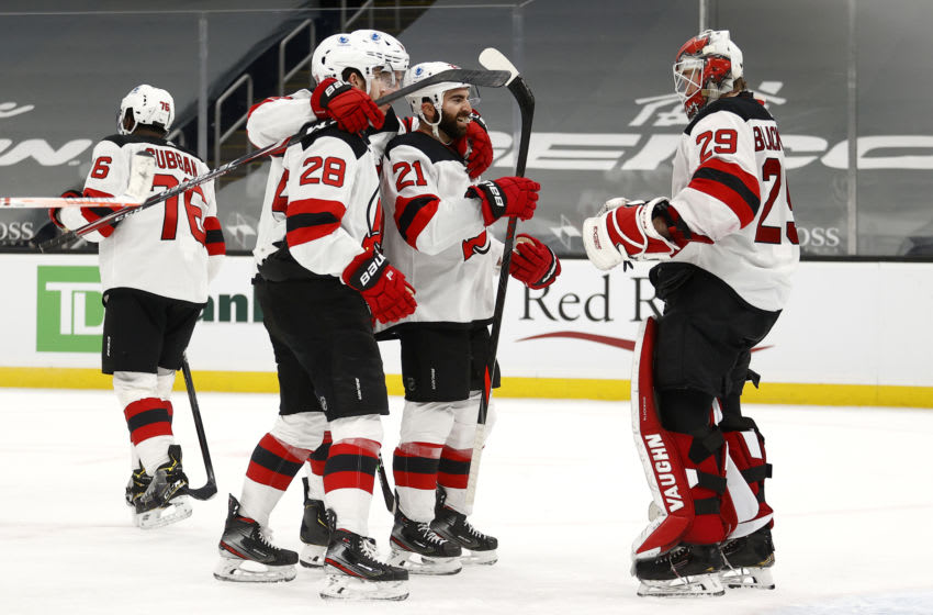 BOSTON, MASSACHUSETTS - FEBRUARY 18: Mackenzie Blackwood #29 of the New Jersey Devils celebrates with Damon Severson #28 and Kyle Palmieri #21 after the Devils 3-1 win over the Boston Bruins at TD Garden on February 18,2021 in Boston, Massachusetts. (Photo by Maddie Meyer/Getty Images)