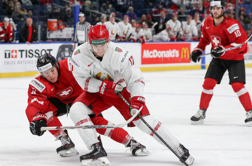 BUFFALO, NY - DECEMBER 27: Yegor Sharangovich #17 of Belarus uses his leg to shield the puck from Elia Riva #17 of Switzerland during the third period of play in the IIHF World Junior Championships at the KeyBank Center on December 27, 2017 in Buffalo, New York. (Photo by Nicholas T. LoVerde/Getty Images)