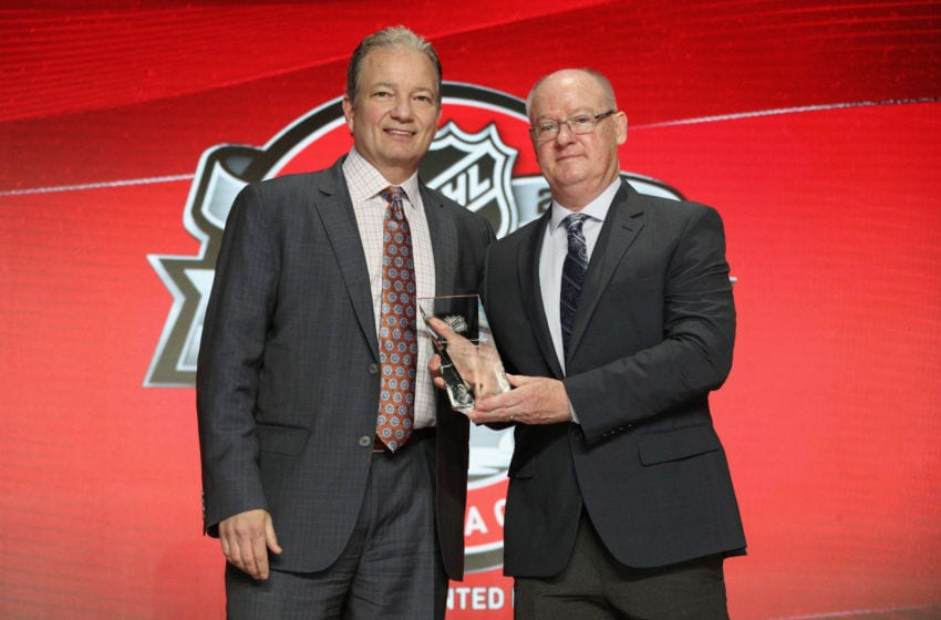 CHICAGO, IL - JUNE 24: Peter Sullivan, a senior scout with NHL Central Scouting (R) presents general manager Ray Shero (L) of the New Jersey Devils on behalf of first draft pick Nico Hischier (not pictured) the E.J. McGuire Award of Excellence before the start of the second round of the 2017 NHL Draft at United Center on June 24, 2017 in Chicago, Illinois. (Photo by Dave Sandford/NHLI via Getty Images)
