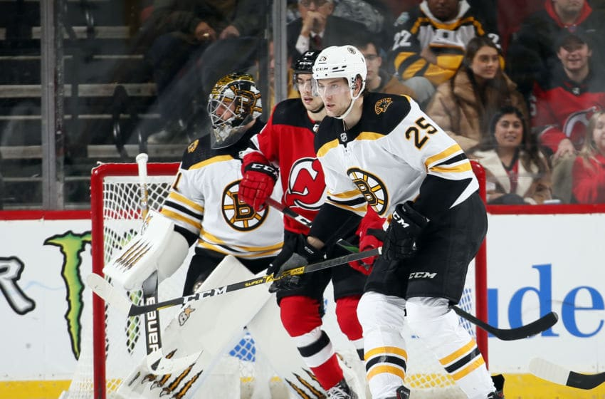 NEWARK, NJ - DECEMBER 31: Brandon Carlo #25 of the Boston Bruins defends against Nico Hischier #13 of the New Jersey Devils during an NHL hockey game on December 31, 2019 at the Prudential Center in Newark, New Jersey. Devils won 3-2 in a shootout. (Photo by Paul Bereswill/Getty Images)