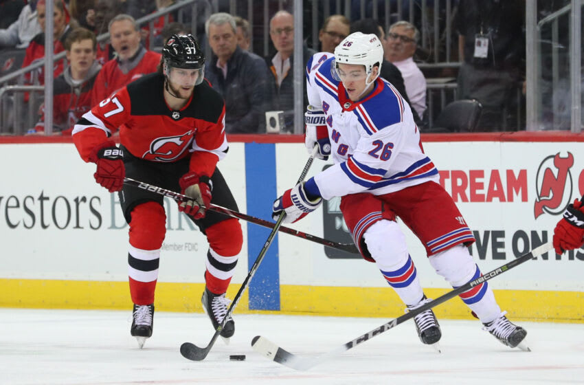 New York Rangers left wing Jimmy Vesey (26) skates with the puck while being defended by New Jersey Devils center Pavel Zacha (37) during the first period at Prudential Center. Mandatory Credit: Ed Mulholland-USA TODAY Sports