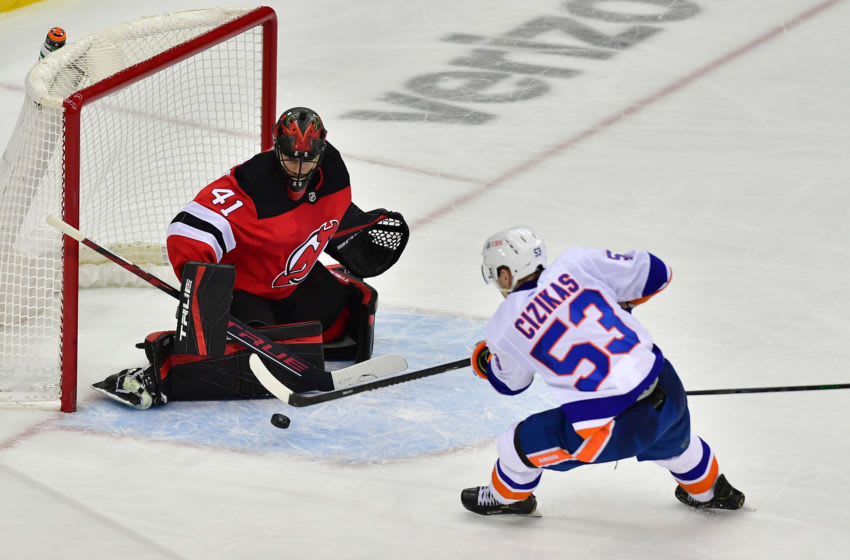 Mar 14, 2021; Newark, New Jersey, USA; New Jersey Devils goalie Scott Wedgewood (41) blocks a shot by New York Islanders center Casey Cizikas (53) during overtime at Prudential Center. Mandatory Credit: Catalina Fragoso-USA TODAY Sports