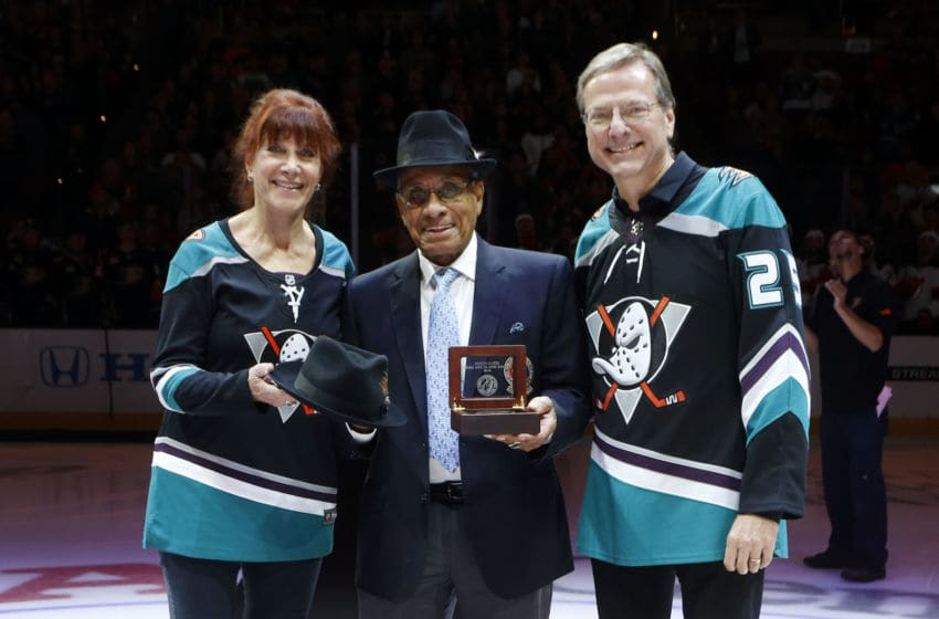 ANAHEIM, CA - DECEMBER 9: Willie O'Ree, center, receives honors and gifts from owners of the Anaheim Ducks, Henry and Susan Samueli prior to the game between the Anaheim Ducks and the New Jersey Devils on December 9, 2018 at Honda Center in Anaheim, California. (Photo by Debora Robinson/NHLI via Getty Images)