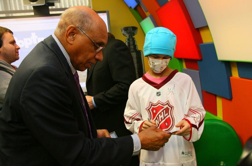 RALEIGH, NC - JANUARY 28: Former NHL player Willie O'Ree signs an autograph for a patient during the Lion's Den
