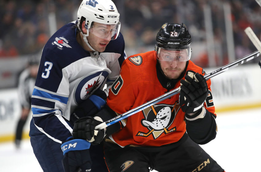 ANAHEIM, CALIFORNIA - NOVEMBER 29: Tucker Poolman #3 of the Winnipeg Jets pushes Nicolas Deslauriers #20 of the Anaheim Ducks during the second period of a game at Honda Center on November 29, 2019 in Anaheim, California. (Photo by Sean M. Haffey/Getty Images)