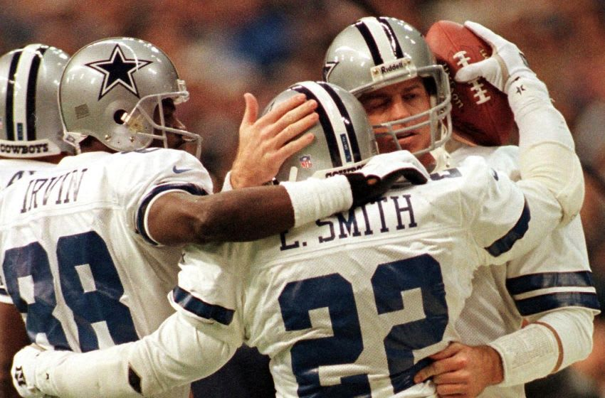 Emmitt Smith of the Dallas Cowboys receives congratulations from teammates Michael Irvin (L) and Troy Aikman (R) after breaking the NFL career touchdown record against the Washington Redskins at Texas Stadium 27 December in Irving, Texas. AFP PHOTO/Paul BUCK (Photo by PAUL BUCK / AFP) (Photo by PAUL BUCK/AFP via Getty Images)
