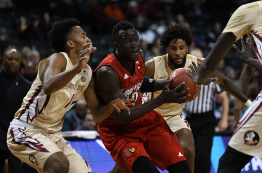 BROOKLYN, NY - MARCH 07: Louisville Cardinals forward Deng Adel (22) drives between Florida State Seminoles defemders during the ACC men's tournament game between the Louisville Cardinals and the Florida State Seminoles on March 7, 2018, at Barclays Center in Brooklyn, NY. (Photo by William Howard/Icon Sportswire via Getty Images)