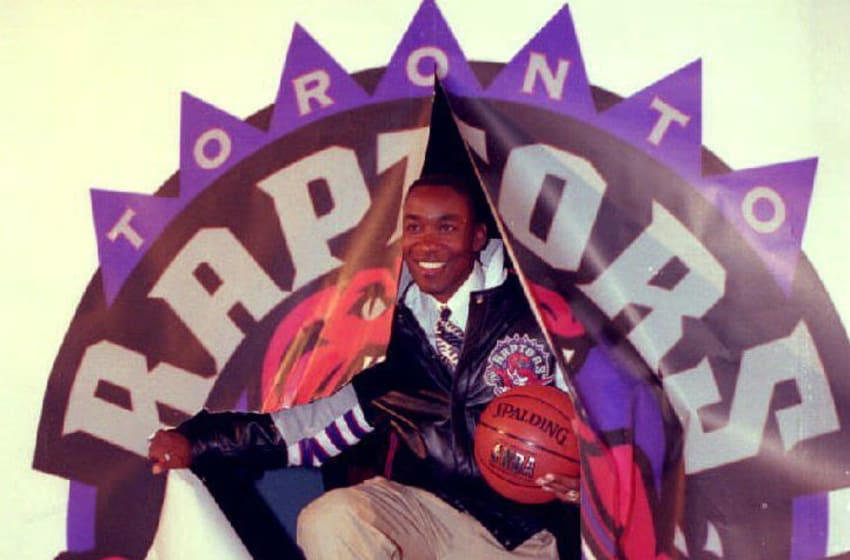 Isaiah Thomas, who retired earlier this month after 13 seasons with the Detroit Pistons, bursts through a Toronto Raptors logo at a press conference 24 May 1994 where it announced that he will be vice-president of basketball operations for the National Basketball Association's (NBA) expansion franchise in Toronto. (Photo by CARLO ALLEGRI / AFP) (Photo credit should read CARLO ALLEGRI/AFP via Getty Images)