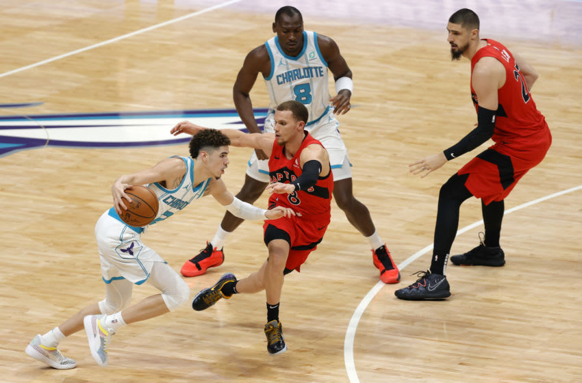 CHARLOTTE, NORTH CAROLINA - DECEMBER 14: LaMelo Ball #2 of the Charlotte Hornets looks to make a move on Malachi Flynn #8 of the Toronto Raptors. (Photo by Jared C. Tilton/Getty Images)