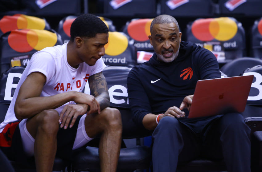 TORONTO, ON - FEBRUARY 24: Patrick McCaw #1 of the Toronto Raptors speaks to Assistant Coach Phil Handy (Photo by Vaughn Ridley/Getty Images)